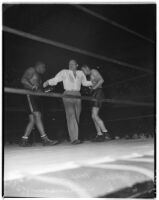 Referee Max Baer stands between George Godfrey and Hank Hankinson during a boxing match at Olympic Auditorium, Los Angeles, August 10, 1937