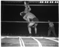 Wrestler and football player Bronko Nagurski flipping challenger Vincent López during a wrestling match at Wrigley Field, Los Angeles, 1937
