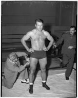 Wrestler and football player Bronko Nagurski having his thigh measured before a wrestling match at Wrigley Field, Los Angeles, August 11, 1937
