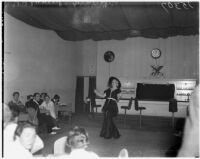 Female impersonator singing to the patrons of a nightclub, Hollywood, circa 1937