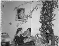 Female impersonator Johnnie David and two unidentified women drinking at a table, Hollywood, circa 1937