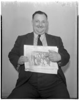 Fred W. Householder, Lucky Lens winner, pointing out a picture of himself in the Evening News, Los Angeles, August 1937
