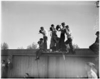 Men perched on a fence at Spaulding Field, UCLA, to photograph the Bruins football team on opening day of the season, Los Angeles, 1937