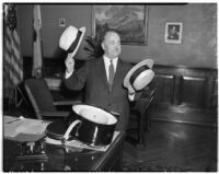 Mayor Frank L. Shaw decides between a bowler hat and a straw hat in his office, Los Angeles, 1930s