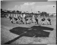 Football players on the Manual Arts High School team run drills during practice, Los Angeles, circa 1937