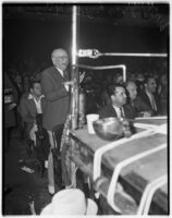 Spectators at a wrestling match, one man stands clapping and yelling, Los Angeles