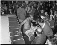 Wrestler King Chewaki falling out of the ring onto referee Dick Rutherford at Olympic Audiorium, Los Angeles, circa 1937