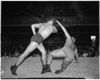 Heavyweight wrestler Vincent López as his opponent falls to the mat during a wrestling match, Los Angeles, 1930s