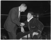 Heavyweight wrestler Vincent López talking to an official in the corner of the wrestling ring, Los Angeles, 1930s