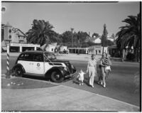 Two women with children cross the street in front of LAPD officers Jack Hoyt and Douglas Gourley, Los Angeles