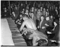 Wrestlers Gino Garibaldi and Ernie Dusek falling out of the ring during at match a Olympic Auditorium, Los Angeles, October 6, 1937