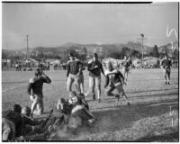 Player pile up during a football game between Franklin and Roosevelt High Schools, Los Angeles, October 8, 1937