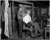 Man gets a haircut from a smiling barber at a cooperative in Los Angeles, 1930s
