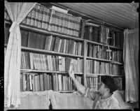 Man takes a book from a bookshelf at the Unemployed Citizens' League of Santa Monica, 1930s