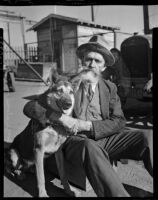 Bearded man sits with a dog at the Unemployed Citizens' League of Santa Monica, 1930s