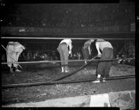 Workers prepare ankle-deep mud in the ring for a wrestling match between Sandor Szabo and Prince Bhu Pinder at Olympic Auditorium, Los Angeles, October 20, 1937