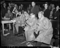 Members of the press dressed in raincoats to protect themselves from mud flying from the ring during a mud wrestling match between Sandor Szabo and Prince Bhu Pinder at Olympic Auditorium, Los Angeles, October 20, 1937