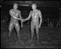 Sandor Szabo and Prince Bhu Pinder shaking hands in the ring after their mud wrestling match at Olympic Auditorium, Los Angeles, October 20, 1937