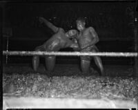 Sandor Szabo puts a hold on Prince Bhu Pinder during a mud wrestling match at Olympic Auditorium, Los Angeles, October 20, 1937