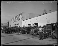 Man stands in front of a row of automobiles at a junk yard and sale outside Eureka Iron & Metal Co., Los Angeles