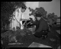 Clifford E. Clinton in a bathrobe investigating a hole in the wall of a house with police officer J.E. Hermans, Los Angeles