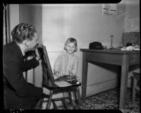 Abandoned child smiles at the camera as an unidentified man looks on, Los Angeles, October 30, 1937