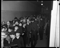 Police regulate a crowd of Robert Noble's supporters who have come to greet Noble as he enters the courthouse to face misdemeanor charges, Los Angeles, November 3, 1937