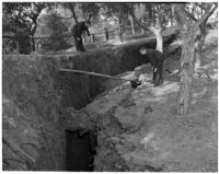 Two men examine a large crack in the earth that would eventually become a landslide in Elysian Park, Los Angeles, November 1937