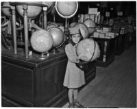 Young girl stands holding a globe in a shop, Los Angeles, 1937