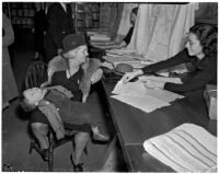 Mrs. Henry Clark looks at fabrics displayed by clerk Lee Maler as baby Warren Hancock sleeps in her lap, Los Angeles, 1925-1945