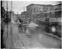 Automobile drives through flooding on Hill St., Los Angeles, December 1937