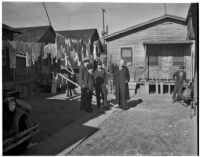 Four well-dressed men stand together in the Los Angeles slums while a fifth man looks on, Los Angeles, 1925-1945