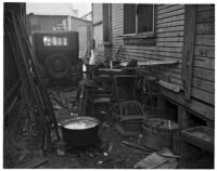 Pile of junk between two buildings in the slums, Los Angeles, 1925-1945