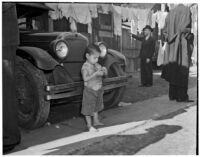 Young boy stands barefoot in front of a car in the slums, Los Angeles, 1925-1945