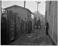 Four men stand aside as a horse-drawn wagon drives through an alley in the slums, Los Angeles, 1925-1945
