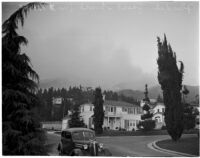 Smoke rises from a forest fire in the Glendale Woodlands, December 20, 1937