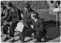 Spectators check their betting sheet on opening day of Santa Anita's fourth horse racing season, Arcadia, December 25, 1937