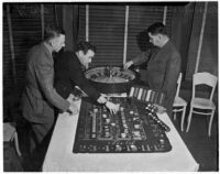 Albert Smith, Jerry Ramlow, and Barney Bernard with gambling equipment confiscated during a police raid on 1019 N. Doheny Rd., Los Angeles, January 1938