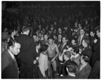 Hungarian wrestler Sandor Szabo walking through the crowd before a match against George Zaharias, Los Angeles, 1930s