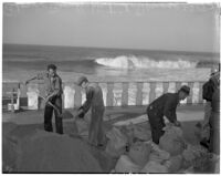 Men fill sandbags at Redondo Beach to protect against heavy seas, January 1940