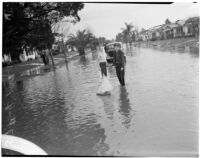 Two boys play with a toy sailboat in a flooded street caused by heavy rainstorms, January 1940