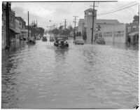 Automobiles drive through flooded streets caused by heavy rainstorms, January 1940