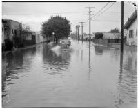 Automobile drives through a flooded street caused by heavy rainstorms, January 1940