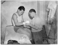 Ceferino Garcia, champion boxer from the Philippines, getting his hand wrapped by a trainer, Los Angeles, circa 1938