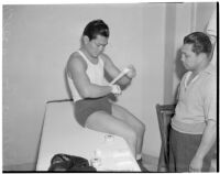 Ceferino Garcia, champion boxer from the Philippines, wrapping his hand with a bandage, Los Angeles, circa 1938