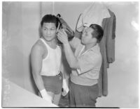 Ceferino Garcia, champion boxer from the Philippines, getting ready for a fight with his trainer, Los Angeles, circa 1938