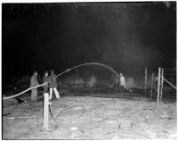 Fire fighters hosing down the former site of the Golden State Fireworks and Display Co. plant after an explosion, February 1940