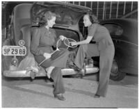 Mrs. Kenneth Holmes and Mrs. Gwynn Fielding with tennis rackets by an automobile, Los Angeles, circa 1940