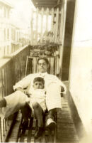 Man with little boy on house balcony