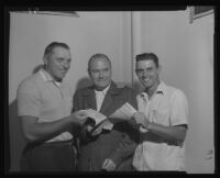 Steve Bilko and Gene Mauch grab a baseball contract from John Holland, Los Angeles, 1956